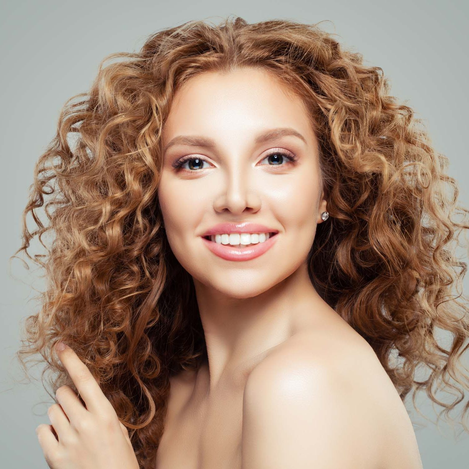 Attractive redhead girl with clear skin and long healthy curly h